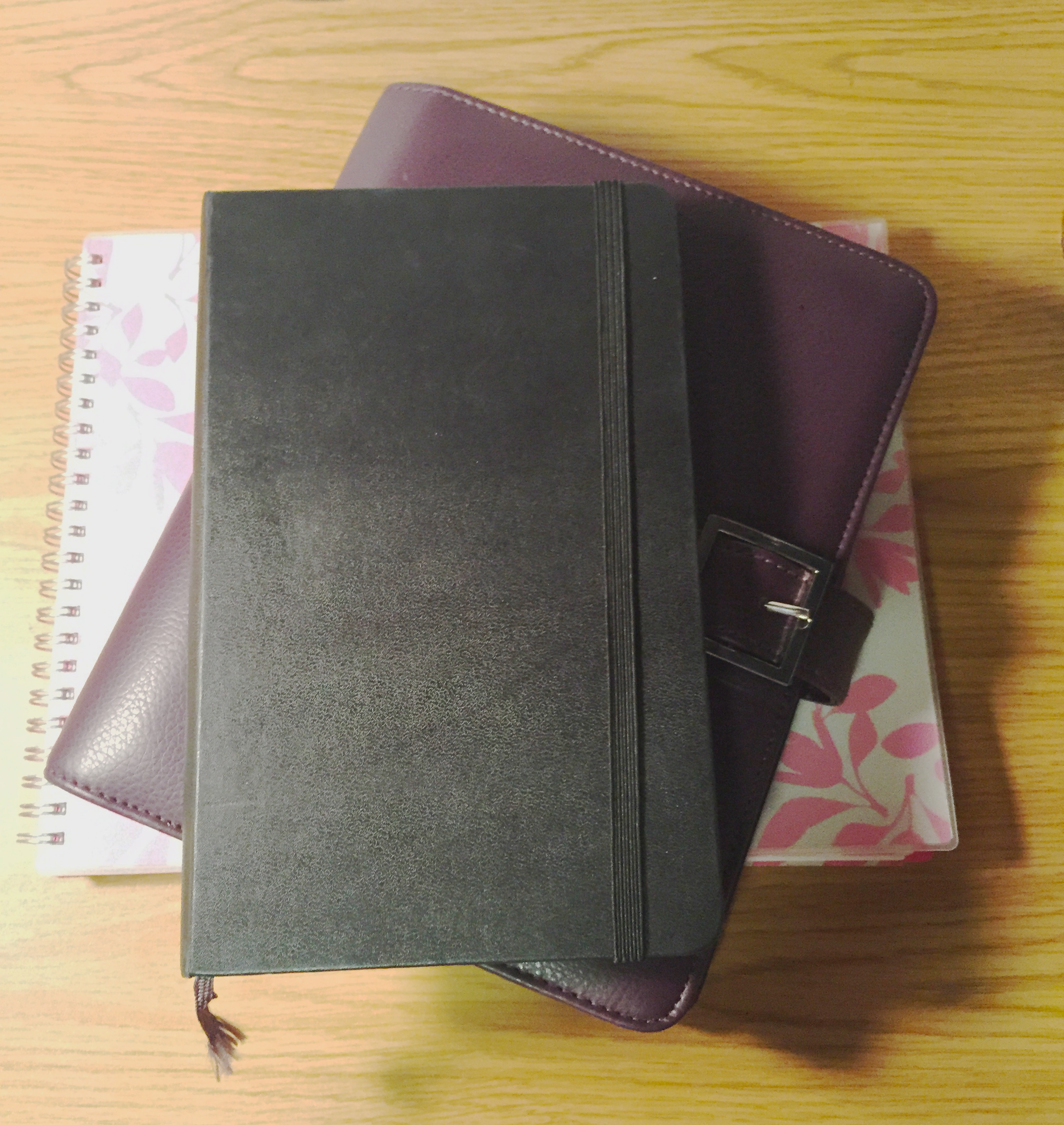 a moleskine, daytimer, and planner from target stacked on each other