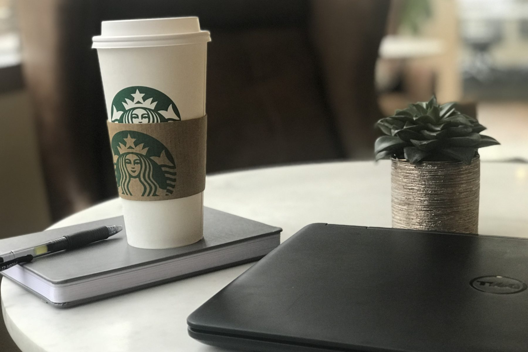 laptop next to a starbucks cup, pen and a notebook
