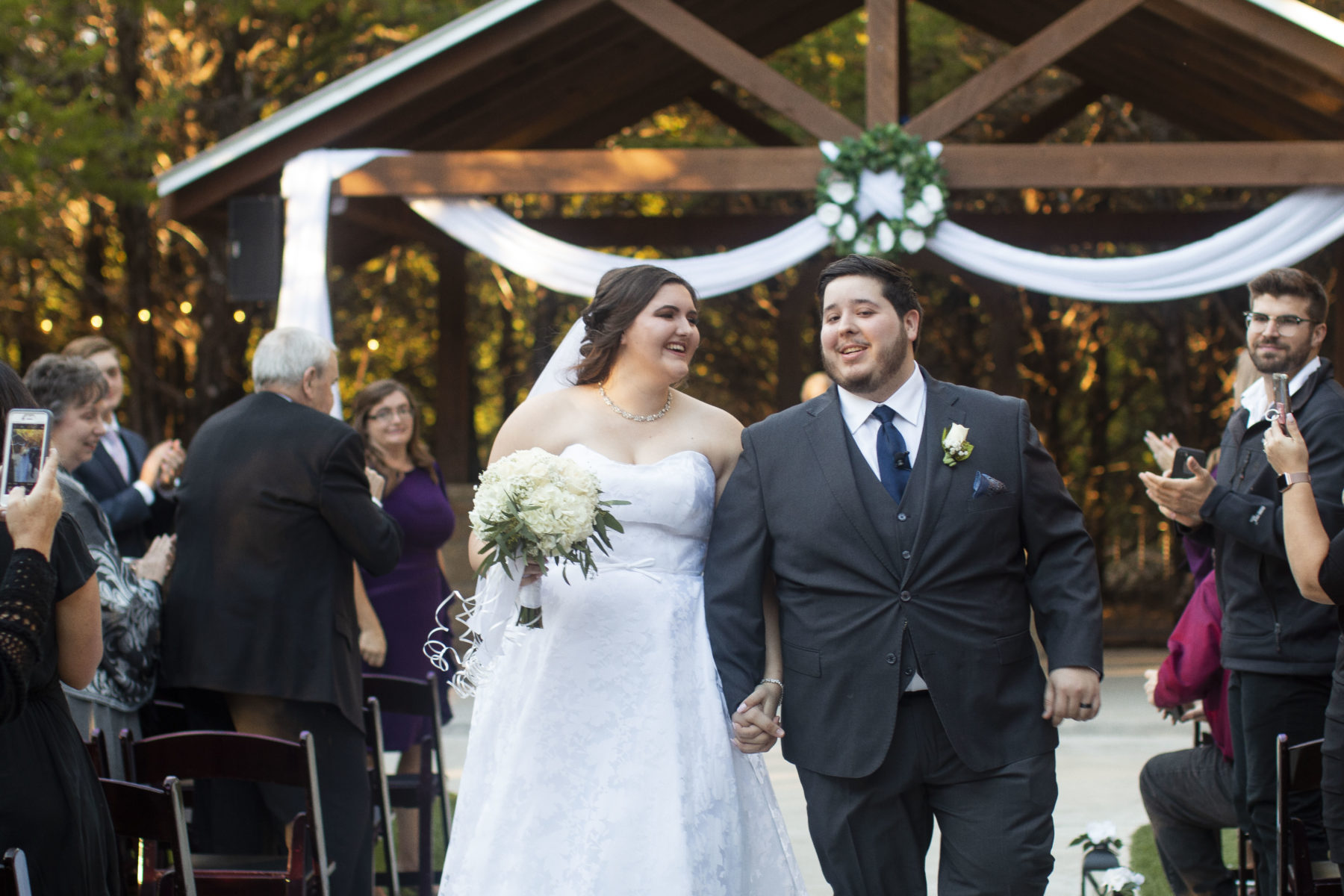 Daniel and I walking down the aisle together laughing and smiling at each other